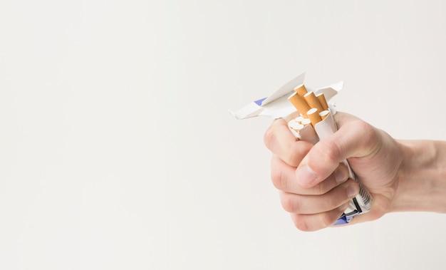 Primo piano della mano di una persona che piega sigarette e scatola