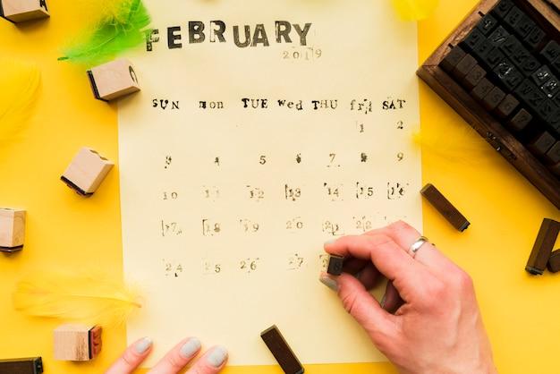 Primo piano della mano di una persona che rende il calendario di febbraio fatto a mano con blocchi tipografici