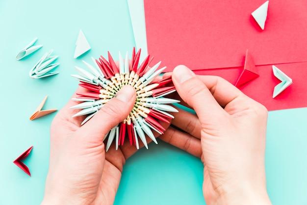 Primo piano della mano di una persona che rende il fiore di carta su sfondo verde acqua