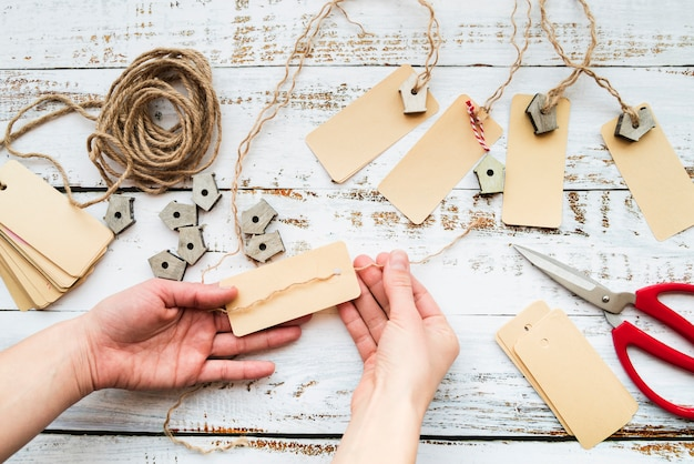 Primo piano della mano di una persona che rende l'etichetta e la ghirlanda birdhouse sul tavolo di legno