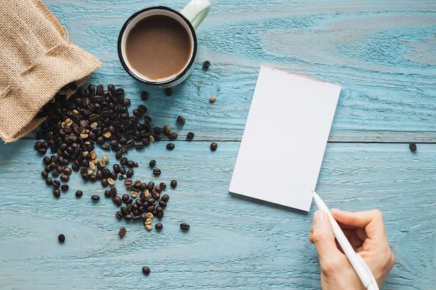 Primo piano della mano di una persona che scrive su carta bianca con tazza di caffè e chicchi di caffè