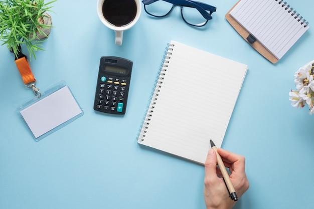 Primo piano della mano di una persona che scrive sul blocco note a spirale con gli articoli per ufficio sopra lo scrittorio blu