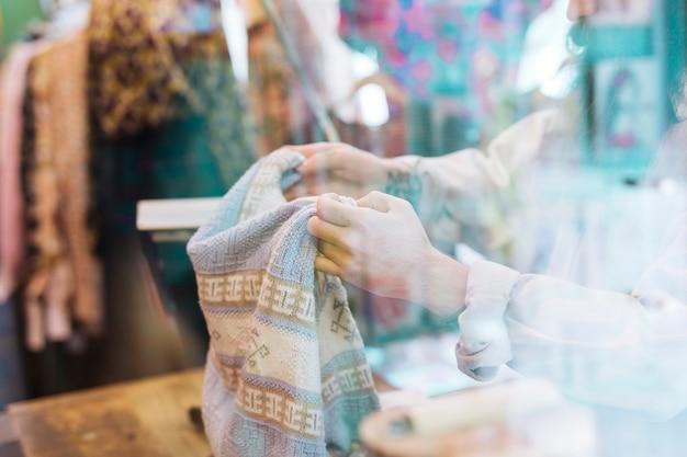 Primo piano della mano di una persona che tiene i vestiti visti attraverso il vetro nel negozio