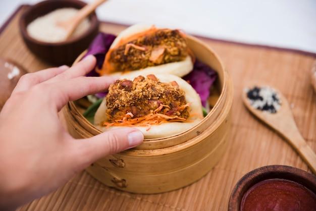 Primo piano della mano di una persona che tiene il bao tradizionale del gua dell'alimento del taiwan in vapore
