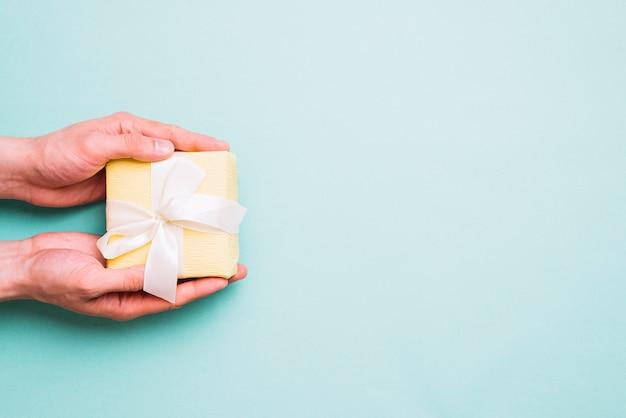 Primo piano della mano di una persona che tiene il piccolo contenitore di regalo su sfondo blu