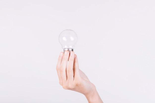 Primo piano della mano di una persona che tiene lampadina su priorità bassa bianca
