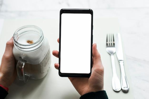 Primo piano della mano di una persona che tiene smart phone con barattolo di frullato
