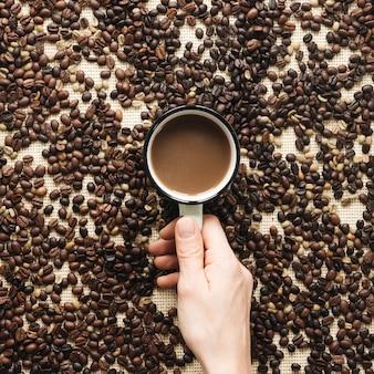 Primo piano della mano di una persona che tiene tazza di un caffè circondato da chicchi di caffè