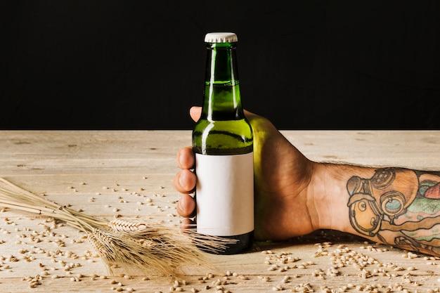 Primo piano della mano di una persona con spighe di grano sulla tavola di legno
