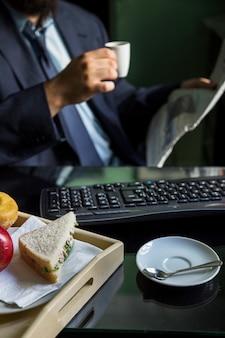 Primo piano della mano di una persona di affari che tiene il giornale della lettura della tazza