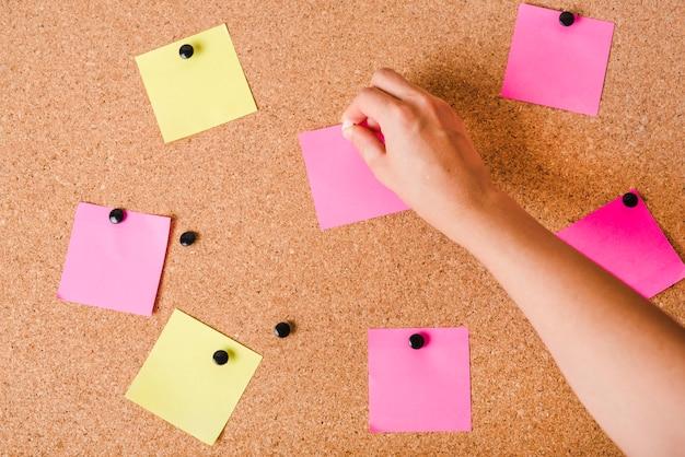 Primo piano della mano di una persona mettendo notepad vuoto sulla scheda del sughero con puntina