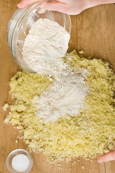 Primo piano della mano di una persona versando la farina in formaggio grattugiato per la preparazione di gnocchi italiani
