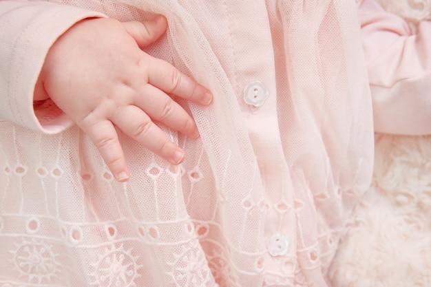 Primo piano della mano di una ragazza appena nata in un abito rosa con pizzi e ricami. cartolina è una ragazza. copyspace