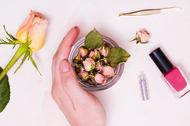 Primo piano della mano femminile che tocca il bicchiere di rosa appassita con una pinzetta; bottiglia di smalto e rosa su sfondo bianco