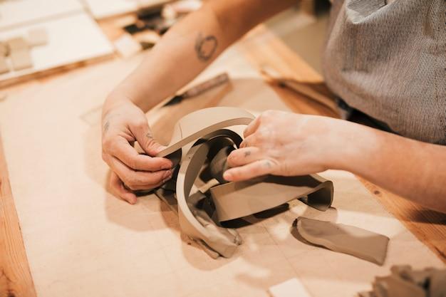 Primo piano della mano femminile del vasaio che lavora l'argilla sulla superficie del tavolo