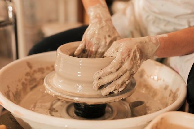 Primo piano della mano femminile del vasaio che modella con l'argilla sulla ruota delle terraglie