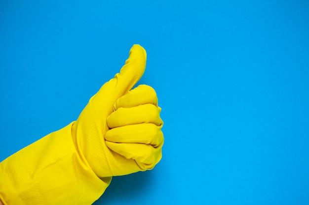 Primo piano della mano in guanti gialli che tengono i rifornimenti di pulizia.