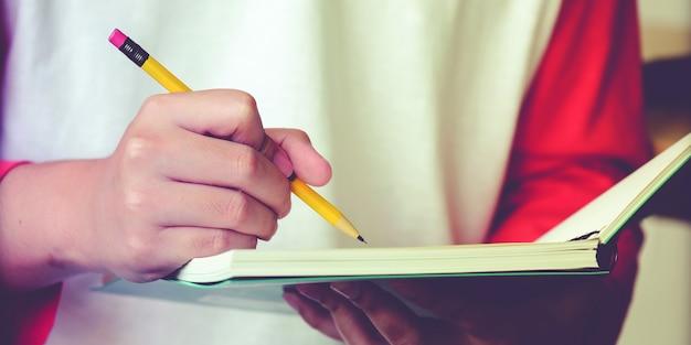 Primo piano della mano liceo o studente universitario in tenuta casual matita scrivendo sul taccuino di carta, studente adolescente mano scrittura libro di appunti di lezione presso il campus della scuola, istruzione universitaria