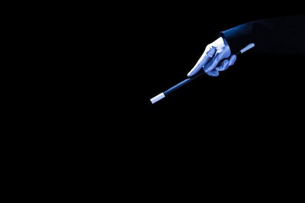 Primo piano della mano magica che tiene la bacchetta magica su sfondo nero