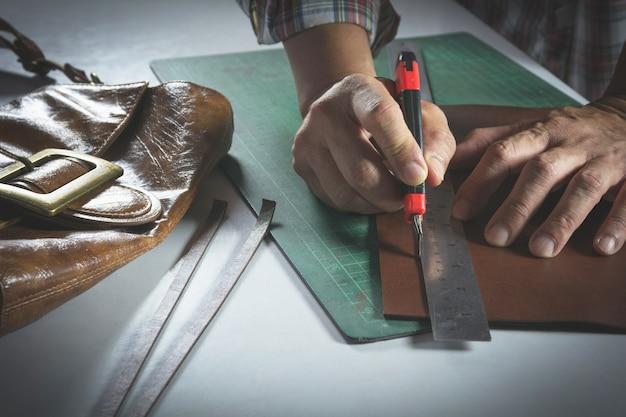 Primo piano della mano maschile che taglia con un coltello alla pelle per la borsa. concetto di prodotto fatto in casa