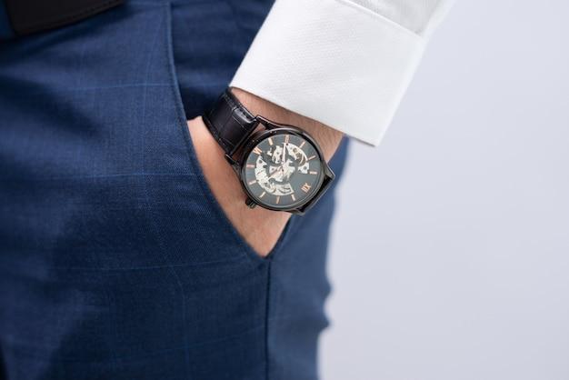 Primo piano della mano maschile in tasca con orologio da polso elegante moderno