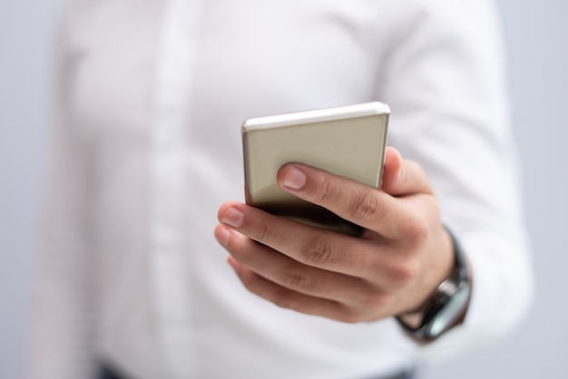 Primo piano della mano maschio che tiene telefono cellulare