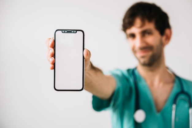 Primo piano della mano maschio di medico facendo uso del telefono cellulare