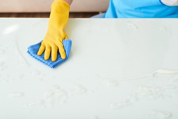 Primo piano della mano nella tavola di pulizia del guanto con il detersivo della schiuma