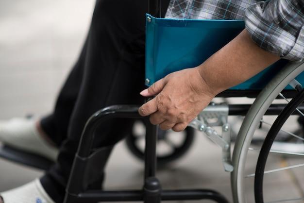 Primo piano della mano senior della donna sulla ruota della sedia a rotelle durante la passeggiata in ospedale