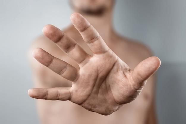 Primo piano della mano sollevata alla fotocamera, gesto di arresto
