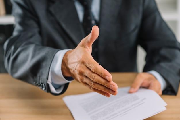 Primo piano della mano tesa dell'uomo d'affari per la stretta di mano
