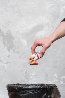 Primo piano della mano umana che getta pacchetto di sigarette