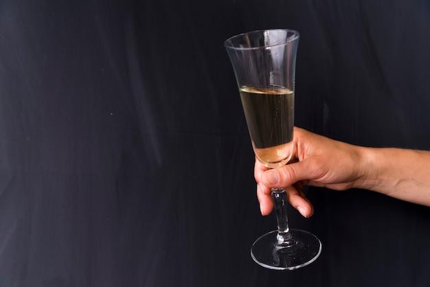 Primo piano della mano umana che tiene il bicchiere di bevanda alcolica su sfondo nero