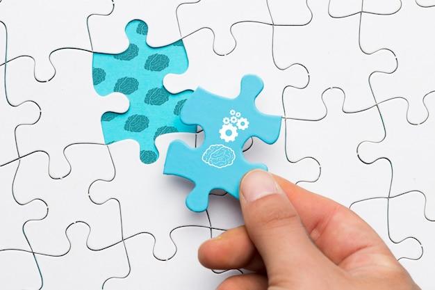 Primo piano della mano umana che tiene il pezzo blu di puzzle con il disegno della ruota dentata e del cervello