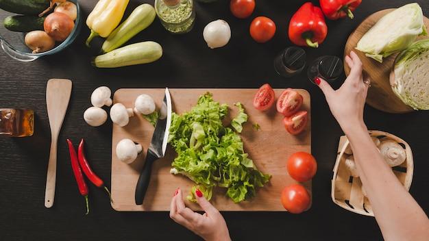 Primo piano della mano umana con verdure colorate su sfondo nero