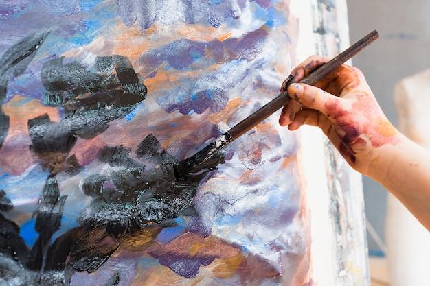 Primo piano della mano umana dipinto su tela con pennello