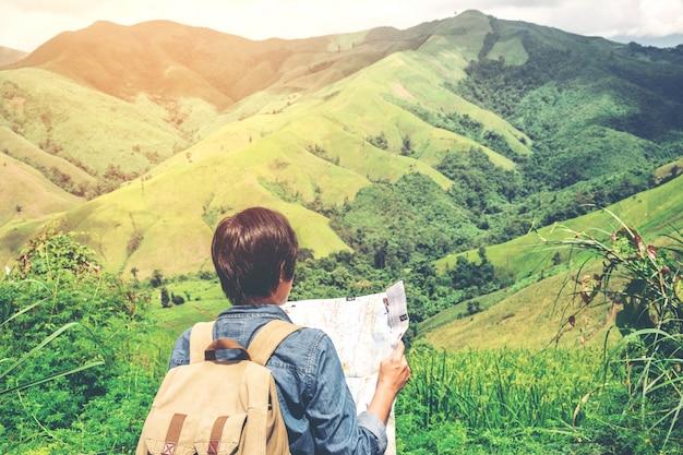Primo piano della mappa della tenuta dell'uomo del viaggiatore dei pantaloni a vita bassa alle montagne con la vista stupefacente