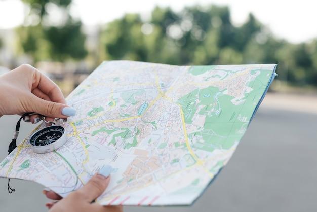 Primo piano della mappa femminile della tenuta della mano e della bussola di navigazione