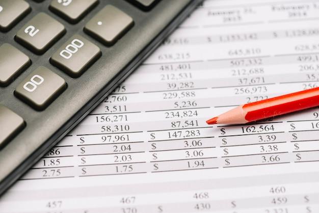 Primo piano della matita colorata rossa con il calcolatore sopra il rapporto finanziario