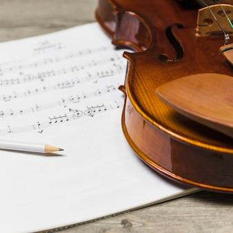 Primo piano della matita e del violino sulla nota musicale sopra la tavola di legno