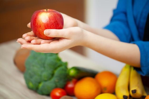 Primo piano della mela della tenuta della donna in mani su fondo delle verdure e della frutta