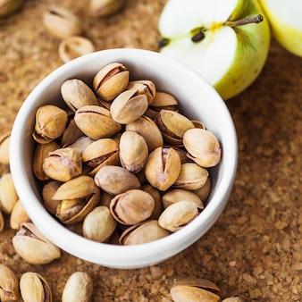 Primo piano della mela divisa in due con la ciotola di pistacchio sulla scheda del sughero