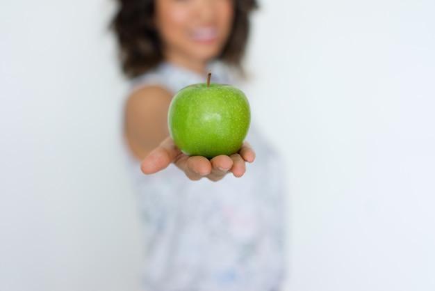 Primo piano della mela verde fresca sulla mano della donna