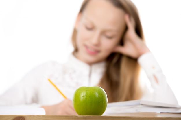 Primo piano della mela verde sulla scrivania