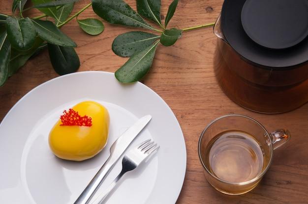Primo piano della mini torta della colla della gomma con la tazza del t sul tavolo