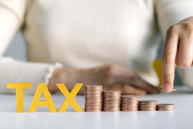Primo piano della moneta della tenuta della mano che mette sulle monete e sulla tassa impilate di parola sulla tavola bianca. concetto di aumento di imposta sul reddito