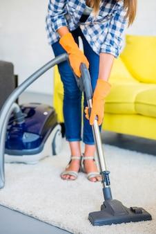 Primo piano della moquette di pulizia della mano di una donna con l'aspirapolvere