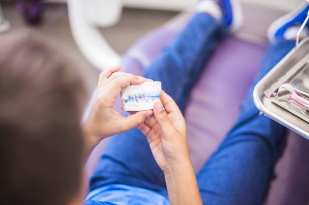 Primo piano della muffa dell'intonaco dei denti della tenuta della mano di un ragazzo