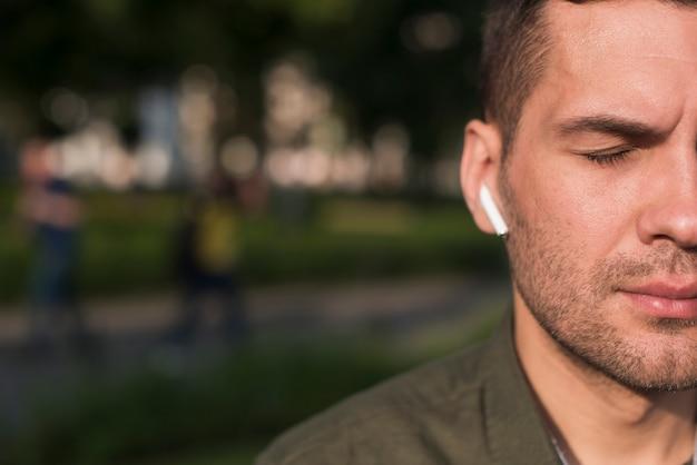 Primo piano della musica d'ascolto dell'uomo con il trasduttore auricolare senza fili