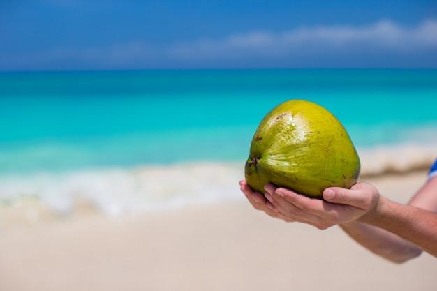 Primo piano della noce di cocco in mani nella spiaggia
